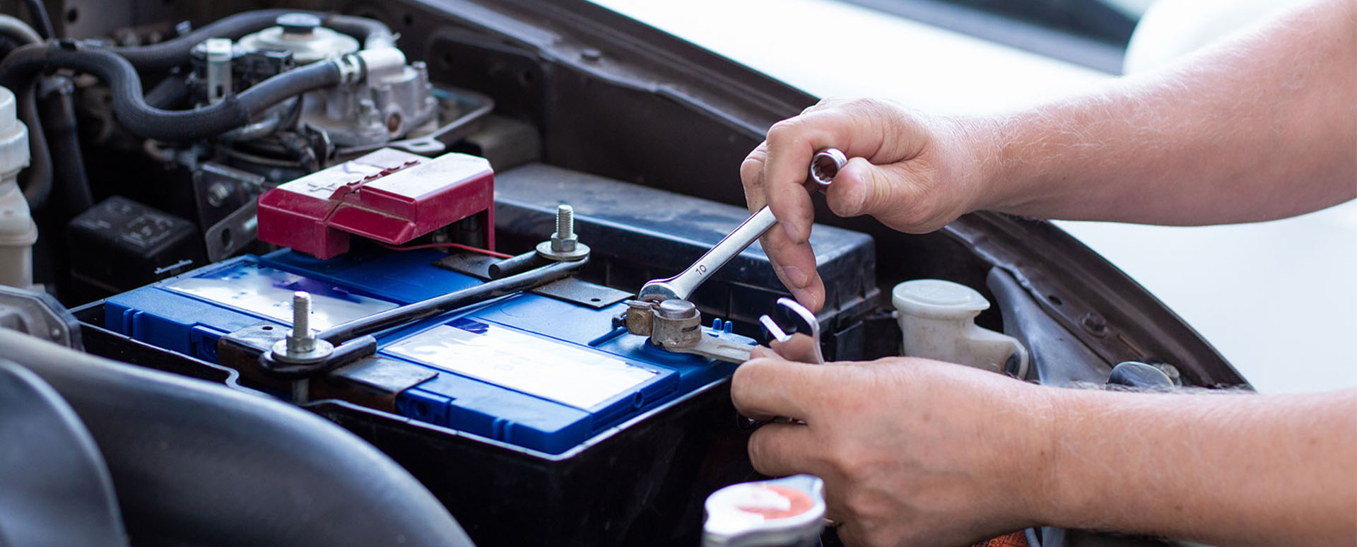 Someone fitting a new battery to a car