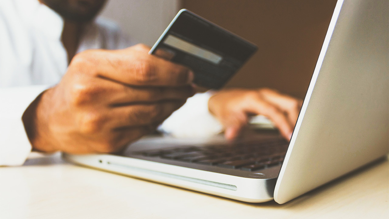 man shopping online and holding payment card