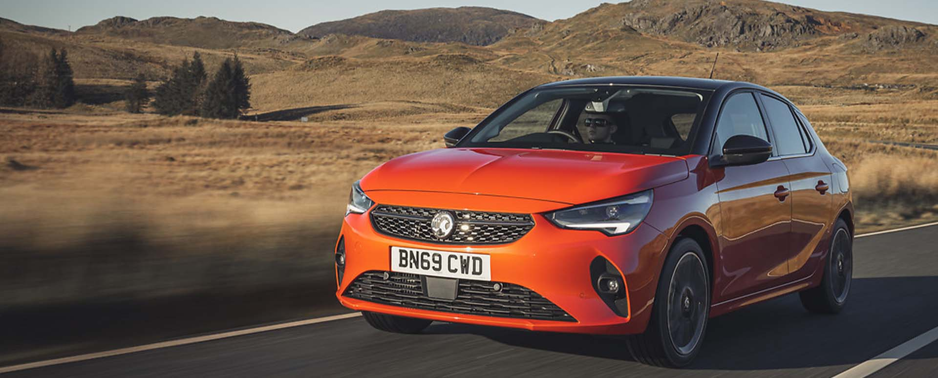 Orange Vauxhall Corsa, driving