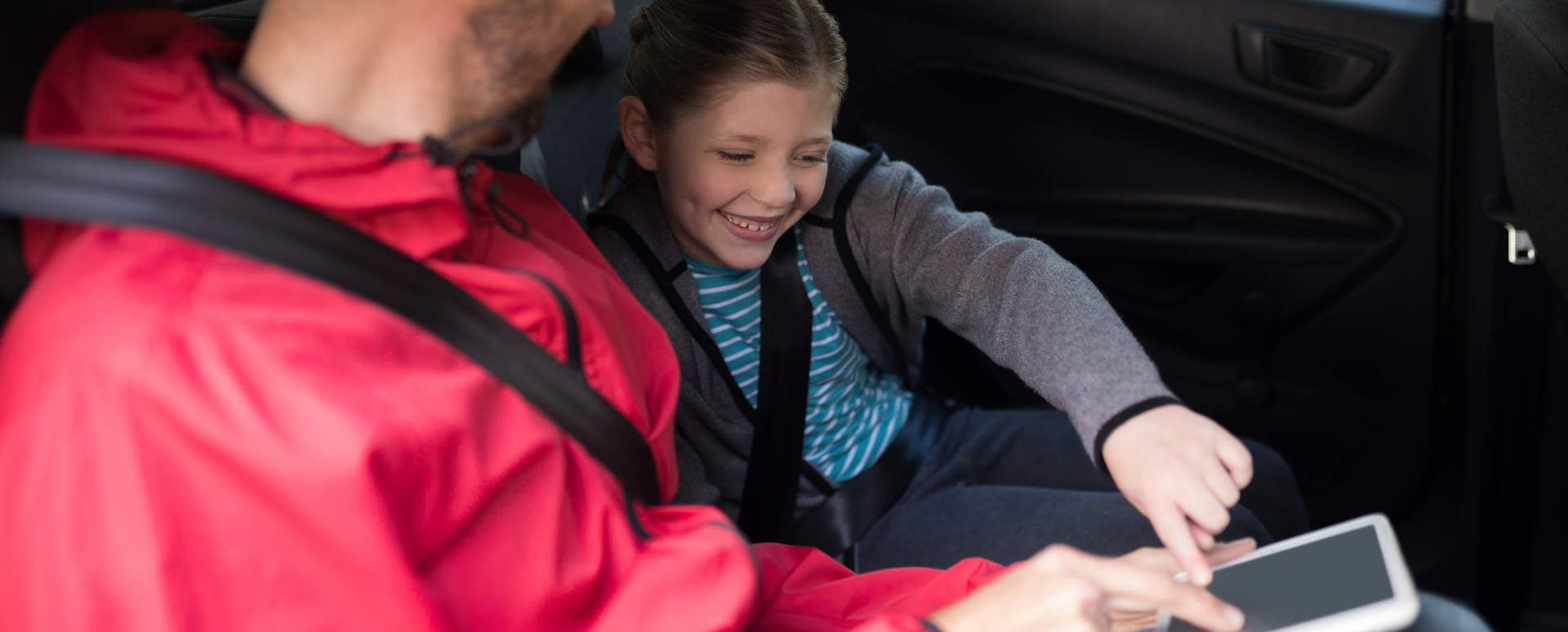 Child with Seatbelt on Playing with iPad