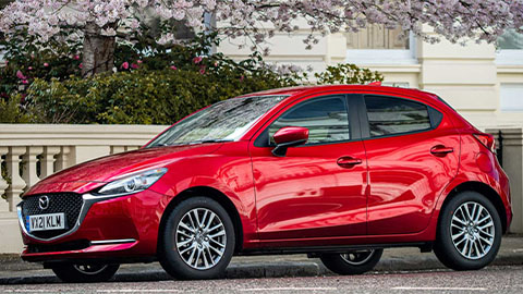 Red Mazda2 parked under a tree