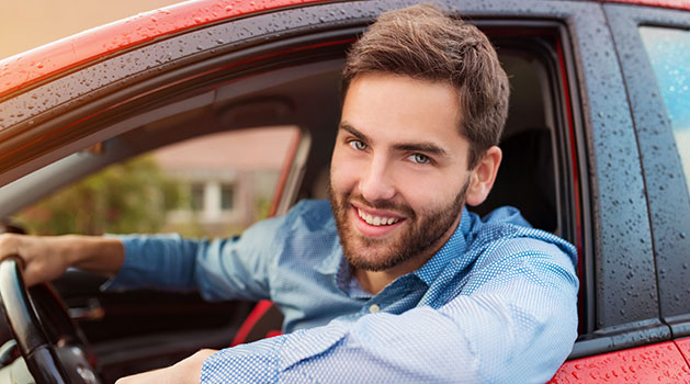 Handsome man leaning out of window with a borderline condescending look on his face. Probably drives a BMW.