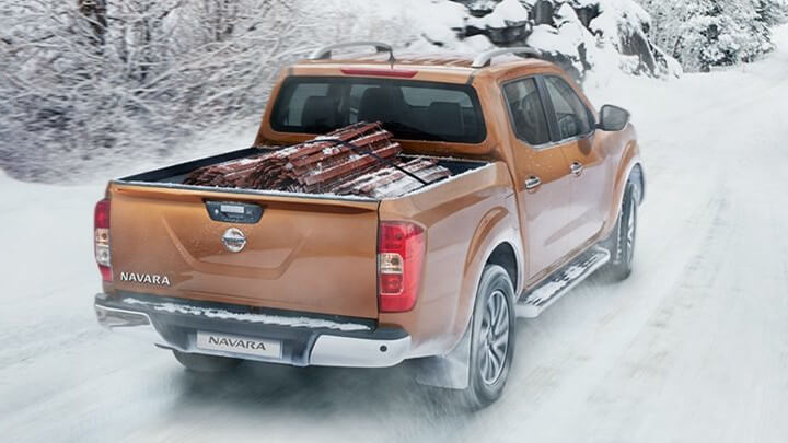 Brown Nissan Navara Driving in the Snow