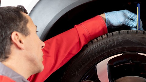 technician checking tyre tread