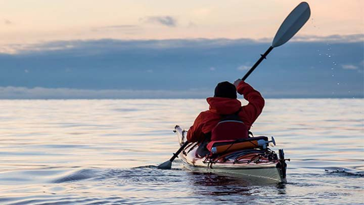 man rowing in kayak
