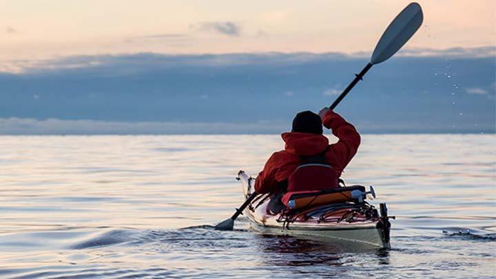 man rowing in kayak