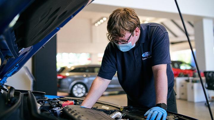 technician inspecting engine bay