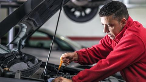 technician checking oil level on engine dipstick