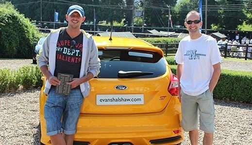Two men posing with a car
