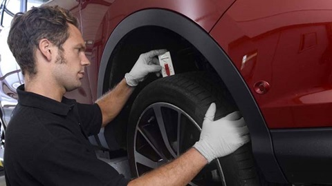 technician inspecting the tread on a tyre