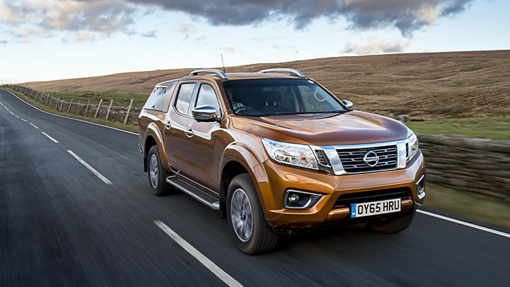 orange nissan navara, driving front quarter