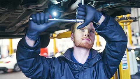 technician servicing underside of vehicle