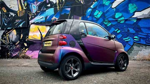 wrapped smart car in front of graffiti wall