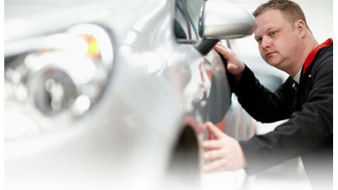 Vehicle Technician looking at a car wanting body shop repairs