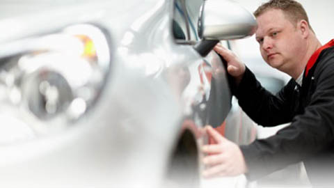 technician inspecting car body work