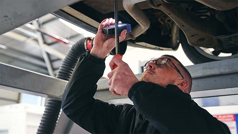 technician checking underside of vehicle during MOT