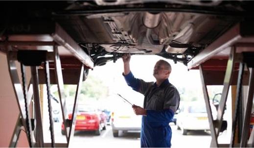 man inspecting under vehicle