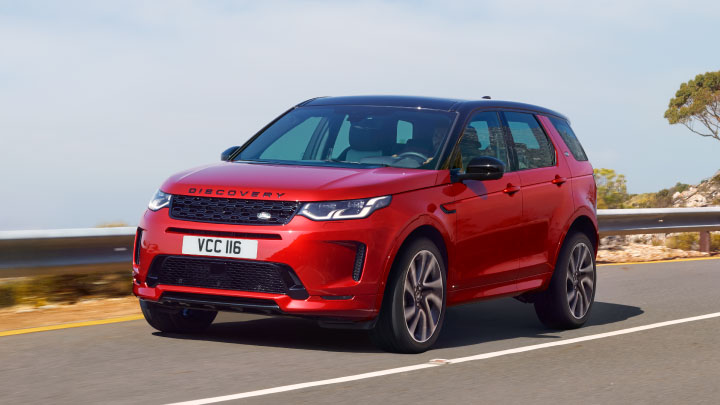 Land Rover Discovery Sport in red driving on the road.