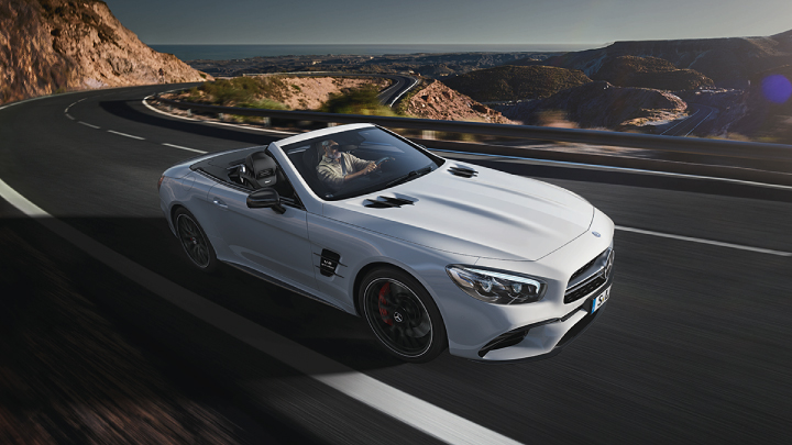 White Mercedes-Benz SL driving on the road.