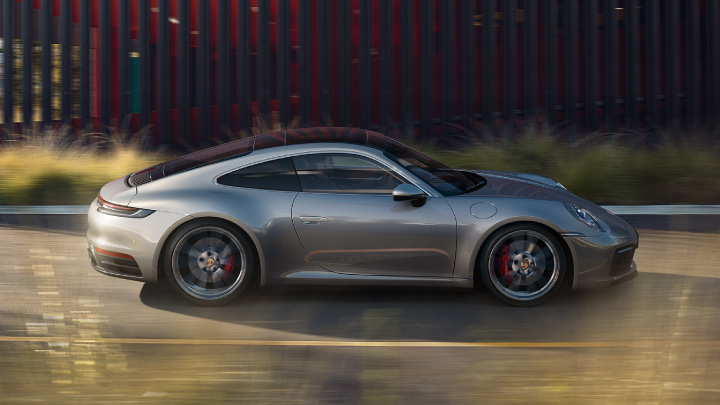 Grey Porsche 911 driving on the road.