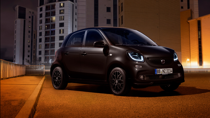 Black smart ForFour parked on the road at night.